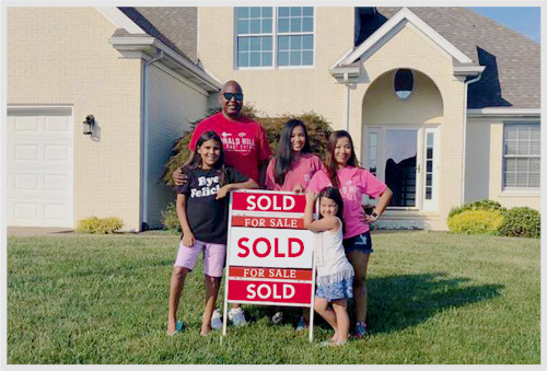 A family gathered around a sold sign in front yard of new home