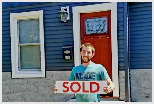Man in front of new home holding a sold sign